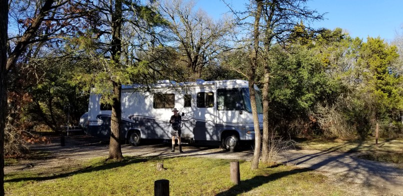 Class A motorhome parked in a campsite at Dinosaur Valley State Park. A man is standing in front of it.