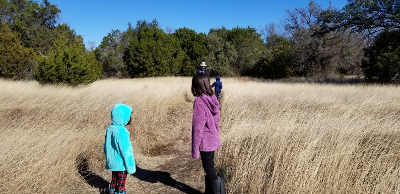 Two girls, a boy, and their father walking on a trail at Dinosaur Valley State Park