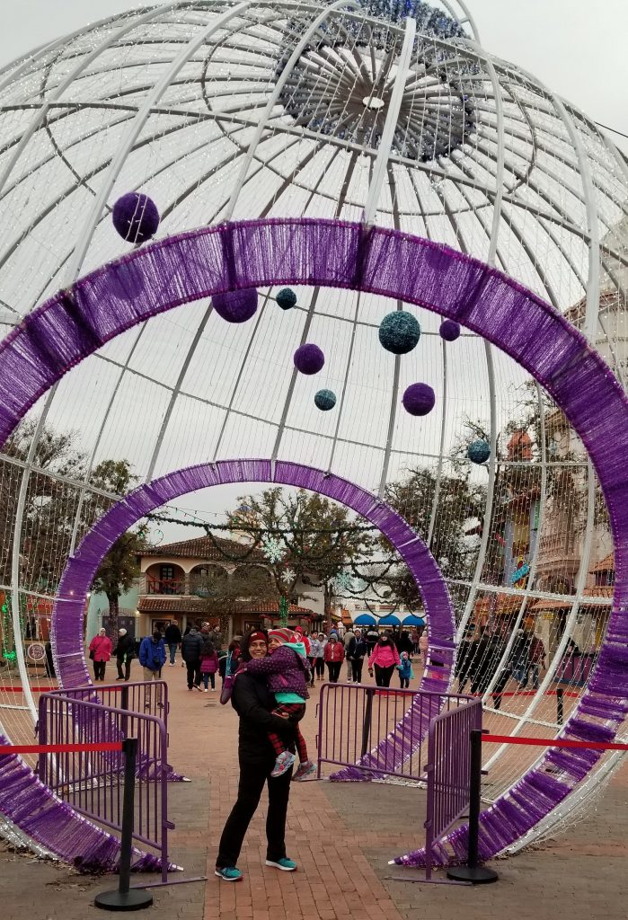 Mother holding daughter in her lap in front of ornament at Six Flags Fiesta Texas Holiday in the Park