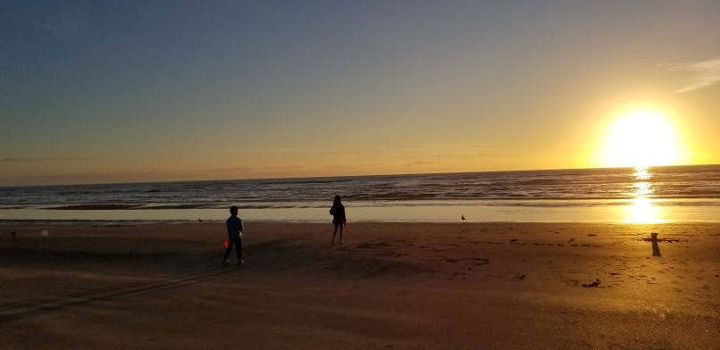 A boy and a girl carrying sand buckers and shovels and watching the sunrise at Padre Balli Park, Padre Island