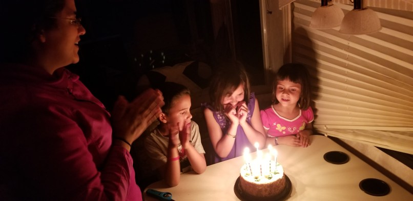 A 6-year-old boy, a 9-year-old girl, and a 4-year-old girl sit around a birthday cake with 9 candles on it. The mother is to the left, clapping her hands. the birthday girl, in the middle, has her hands under her chin.