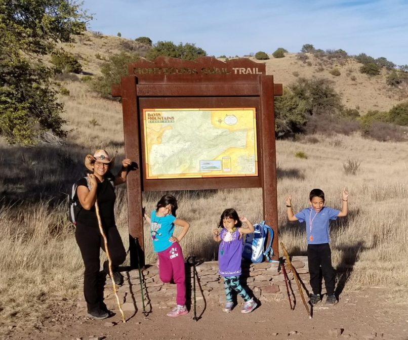 A family poses by the a Trail sign at Davis Mountain State Park. The mother is wearing a black t-shirt, black pants, a pink cowboy hat, and a grey and black backpack. She is holding a wooden walking stick. A 9-year-old daughter poses by the sign, along with her 4-year-old sister and 6-year-old brother.