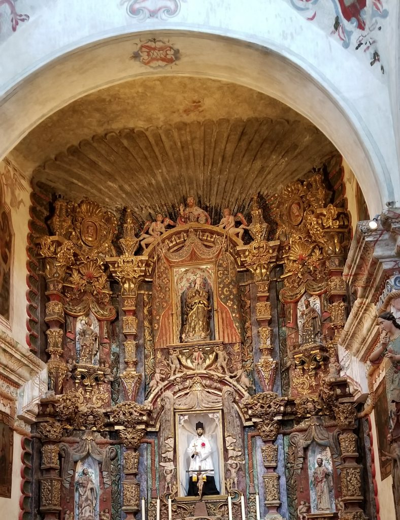 San Xavier del Bac sanctuary. several statues and ornate details in gold under an archway.