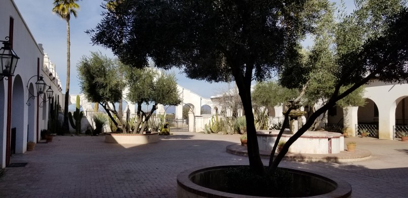 garden at San Xavier del Bac Mission, Arizona. Trees and a fountain can be seen, with an arched wall at the back.