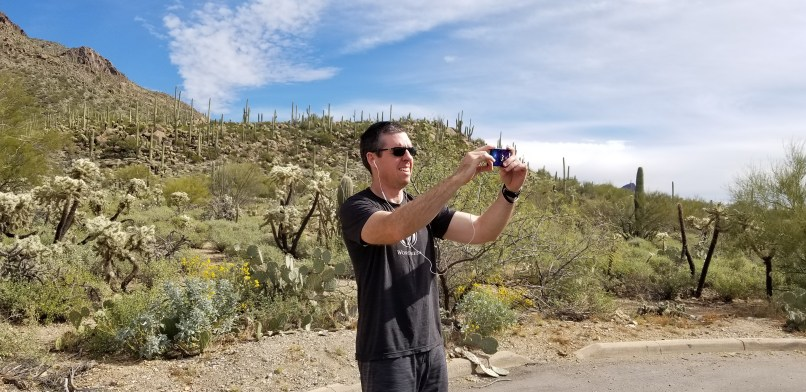 A man is standing in front of a hill covered in desert plants. He is wearning a gray t-shirt and shorts, and is wearing sunglasses and ear buds. He is holding up a phone and smiling into it.