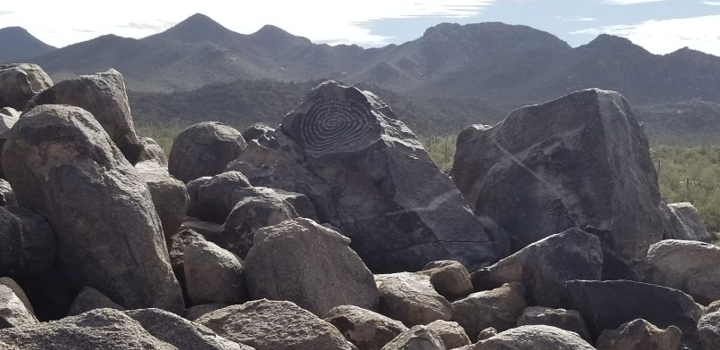 A group of rocks. The rock that stands above all the others has a spiral petroglyph etched on it.