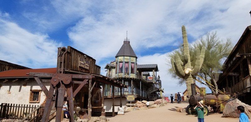 Goldfield Ghost Town. A brown building and a green building are on the left, and a saguaro cactus can be seen on the right.