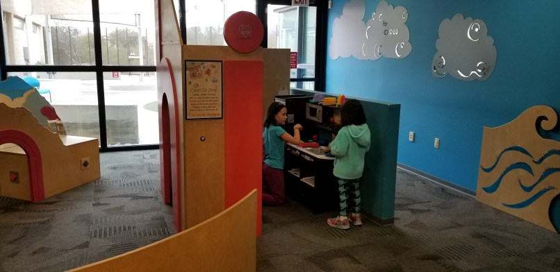 Two girls play in the preschool area of the Apache Junction library. They are playing at a play kitchen.