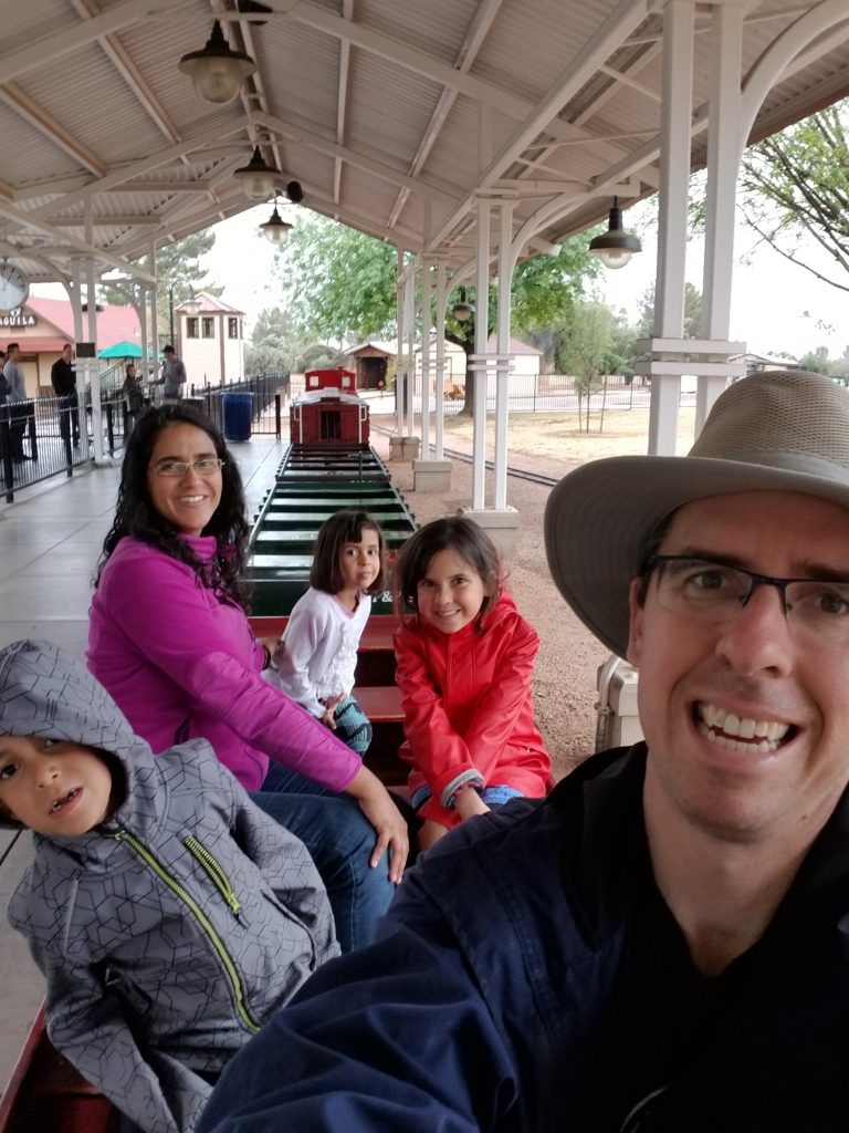Father, mother, 6-year-old son, 9-year-old daughter, and 4-year-old daughter sitting on the mini train at the McCormick-Stillman Railroad Park in Scottsdale, Arizona.
