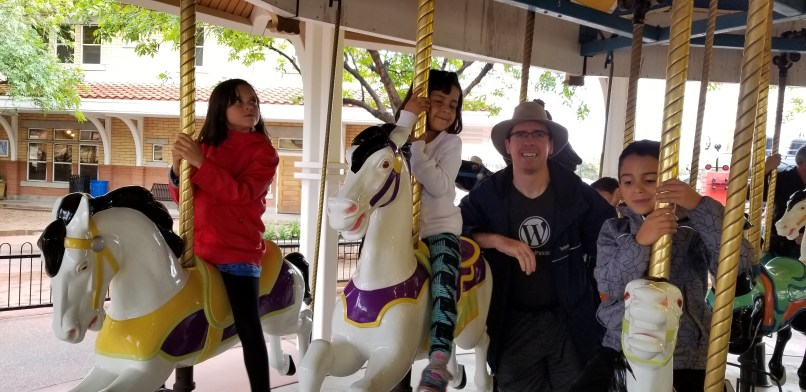 Two girls and a boy riding on carousel. Their father is standing in between one of the girls and the boy.