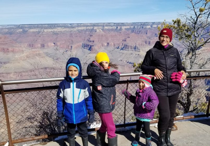 A mother and her 4-year-old daughter, 6-yer-old son, and 9-year-old daughter try to pose for a photo in front o f the Grand Canyon lookout.