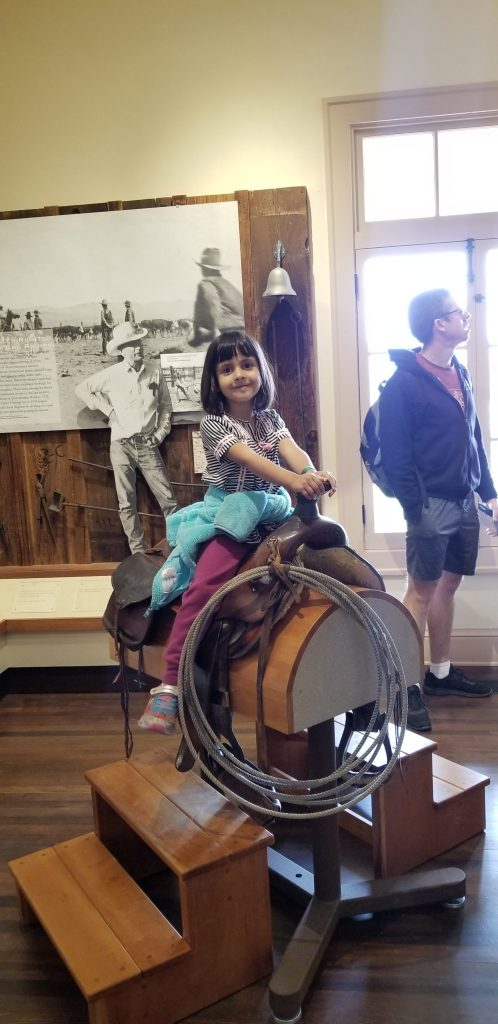 Girl sitting on a saddle at Mojave National Preserve Visitor Center