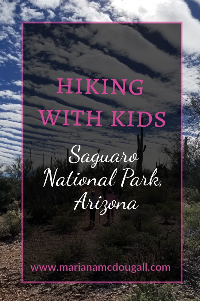 Pinterest Title Image. Pink and white letters read: Hiking with Kids, Saguaro National Park, Arizona, www.marianamcdougall.com. Background photo by Mariana Abeid-McDougall shows father and three young childrne hiking on a trail at the park. A saguaro cactus can be seen in the distance.