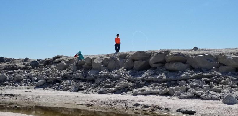 boy and birl climbing rocks at the salton sea