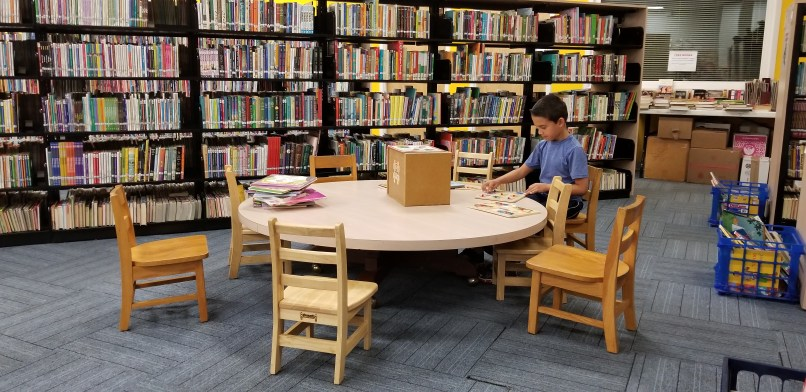 boy doing a puzzle at a table in front of a shelf of books.