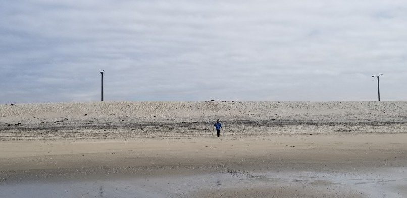 Boy walking with two sticks on sand at Silver Strand Beach