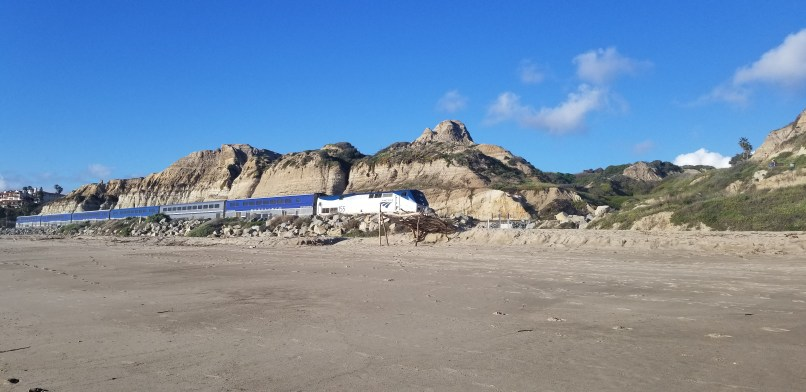 A train passing by in front of mountains at San Clemente State Beach, California