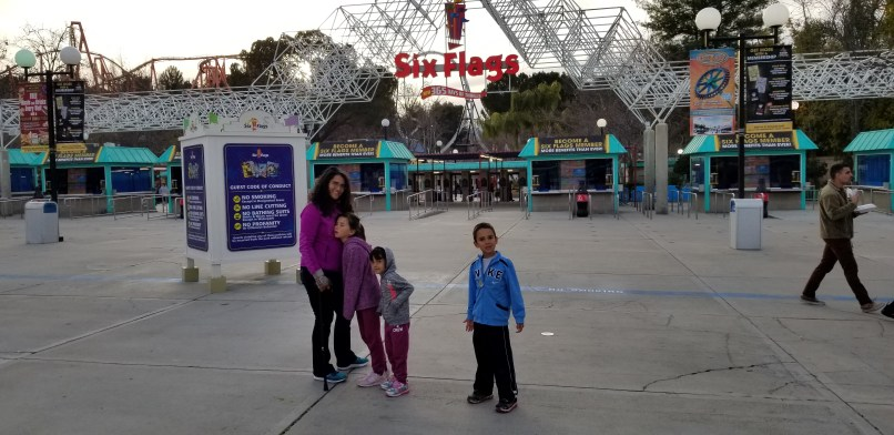 Mother, two daughters and a son standing at the entrance to Six Flags Magic Mountain. The mother is holding a cane.