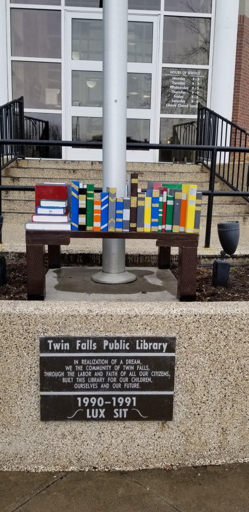 Twin Falls Public Library entrance, sculpture of books and a commemorative plaque.