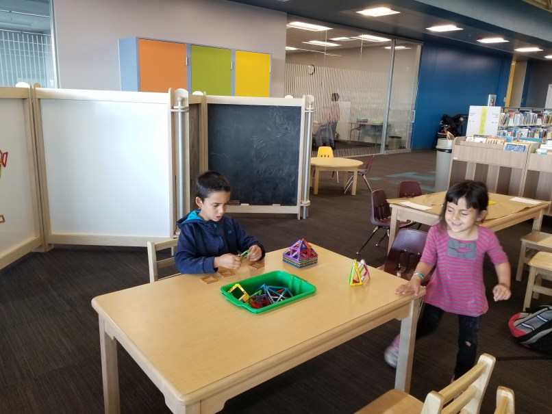 A 6-year-old boy and a 4-year-old girl play with magnetic shapes at a table at the Crowfoot Branch of the Calgary Public Library.