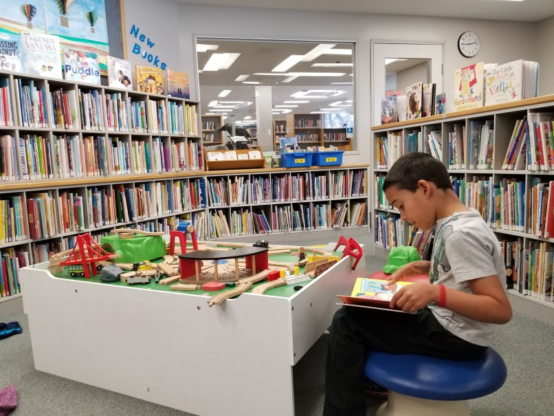 6-year-old sitting by a train table and reading a book at the children's section of the Moose Jaw Public Library