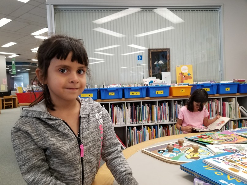 4-year-old girl smiling at the camera while a 9-year-old girl reads at a table in the background at the Moose Jaw Public Library in Moose Jaw, Saskatchewan