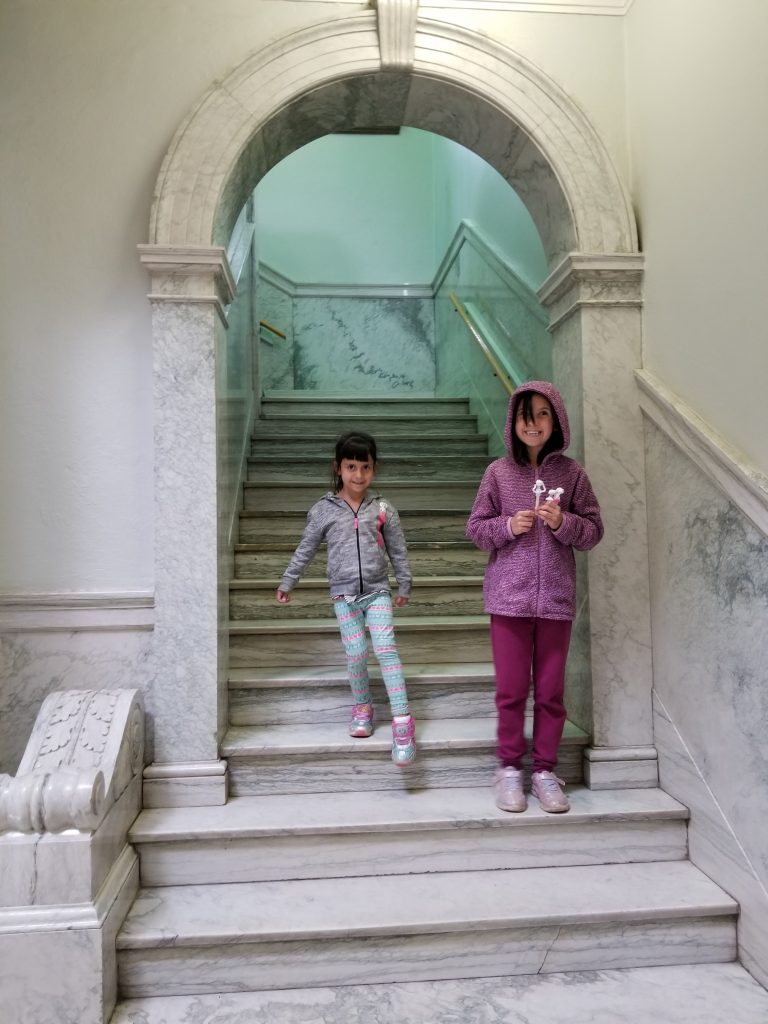 A 4-year-old girl and a 9-year-old girl go down the marble steps at Moose Jaw Public Library. They are exiting an arched entryway.
