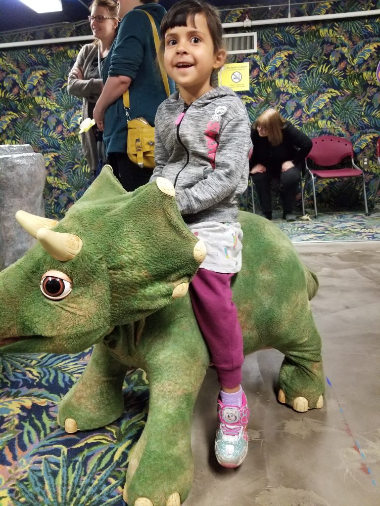 4-year-old girl riding a toy dinosaur