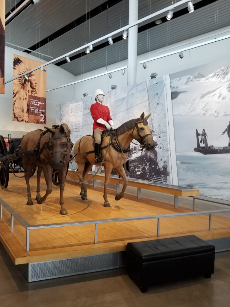 """RCMP Heritage Centre display showing statues of horses with a """"mountie"""" atop one."""