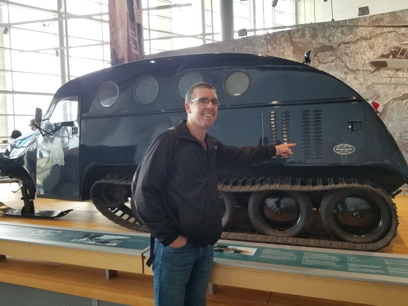 "Man standing in front of a Bombardier snow vehicle, pointing at the ""Bombardier"" trademark on the side. RCMP Heritage Centre, Regina, Saskatchewan"