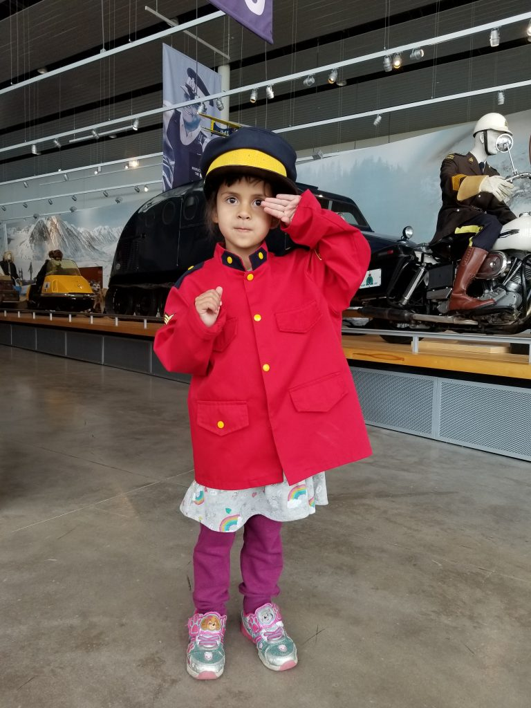 4-year-old girl dressed up in a RCMP jacket and cap salutes to the camera at the RCMP Heritage Centre in Regina, Saskatchewan