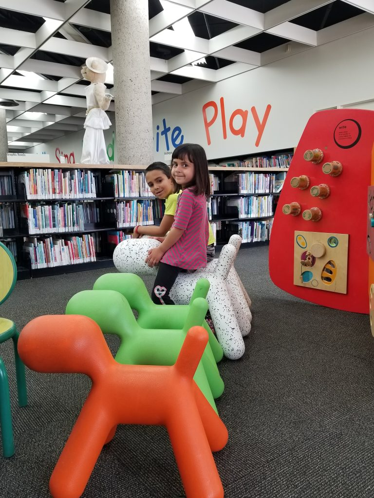"A 6-year-old boy and a 4-year-old girl sitting on ride-on dogs at the Winnipeg Millenium Library. Stacks of book can be seen behind the children, and the words ""Write"" and ""Play"" are written on the wall."