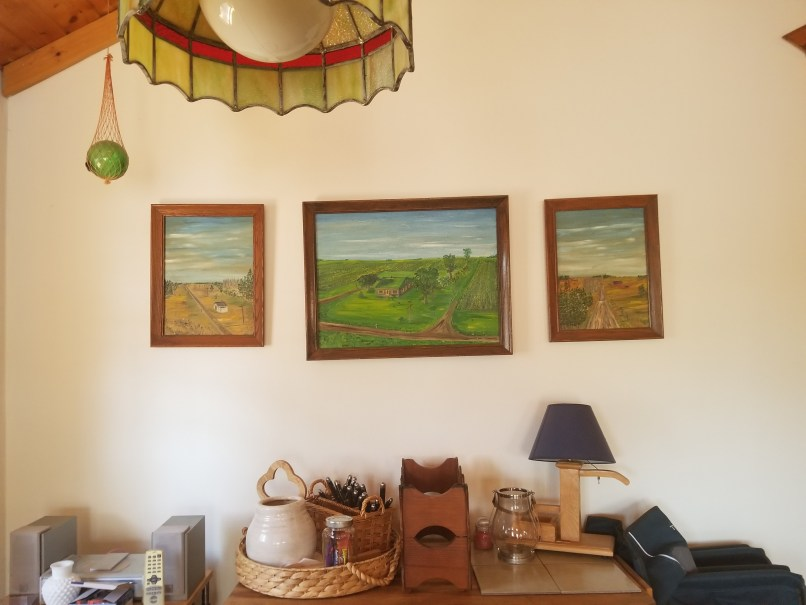 A wall showing 3 paintings of farms.