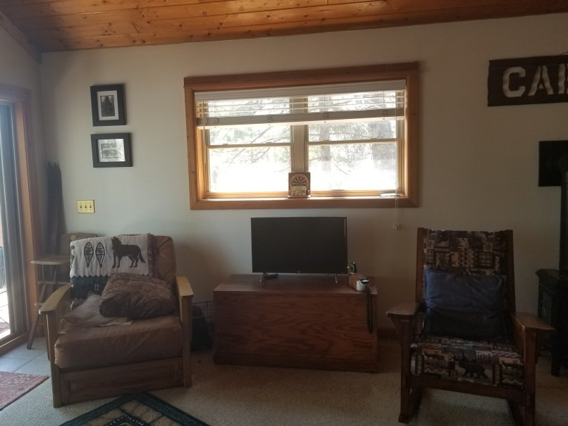living room in a cabin shows a TV under a window, with chairs on either side.