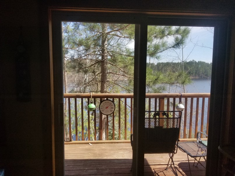 View from sliding door at a cabin: the lake can be seen from the glass.