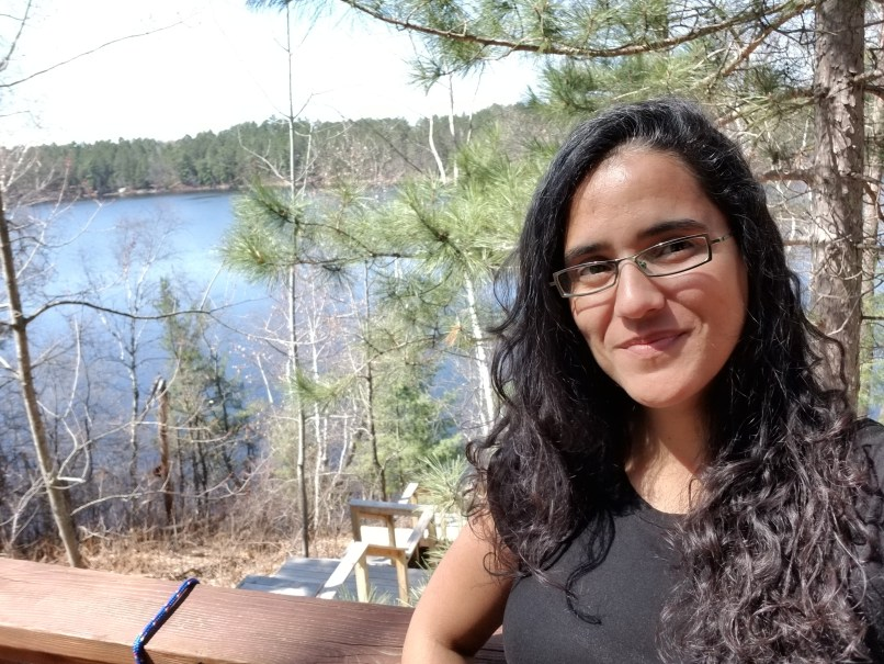 Woman with long black hair takes a selfie with the lake behind her