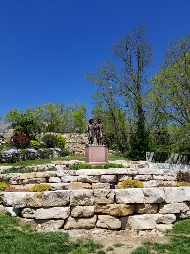 A rock garden with a statue on top, with a background of a very deep blue sky.