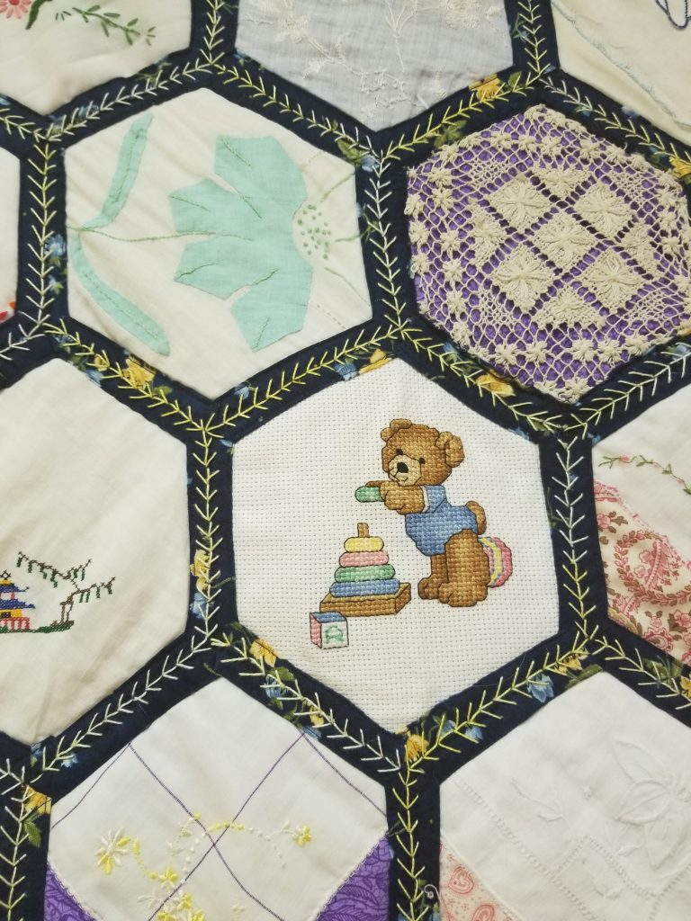 Embroidery detail on honeycomb quilt