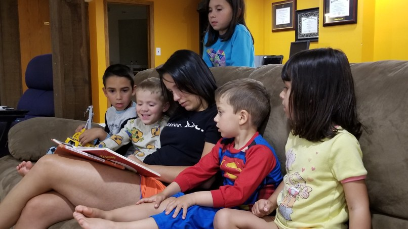 woman reading to children on the coach