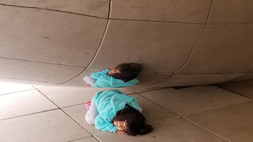 4-year-old girl crouching under The Bean sculpture at Millennium Park, Chicago
