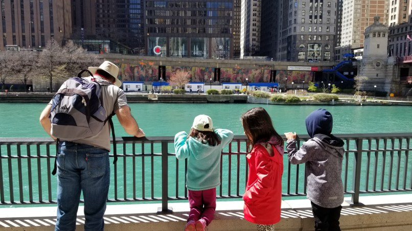 Father and three children looking at Chicago River from the Riverwalk