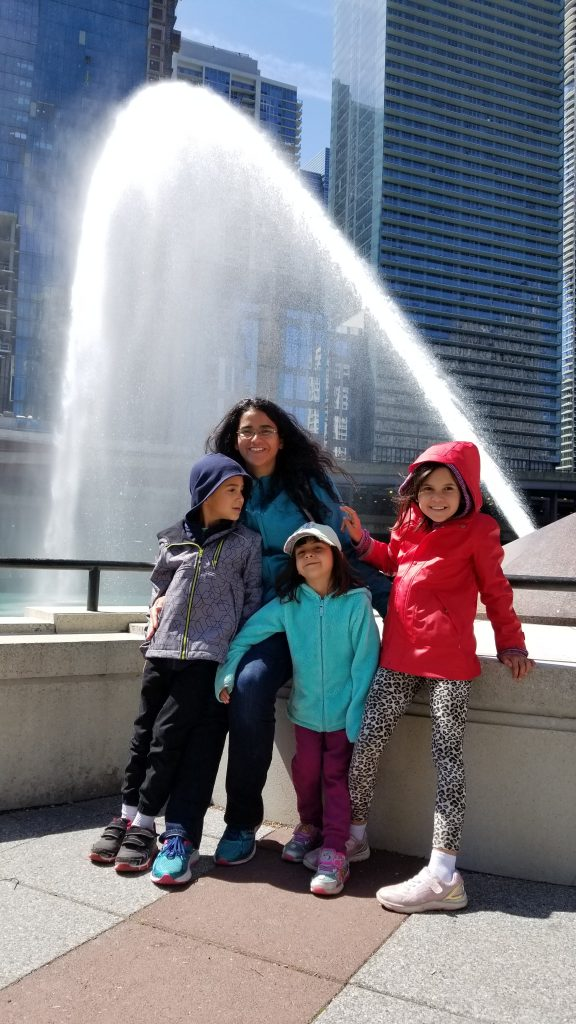 Mother with three children in front of the Centennial arc in Chicago.