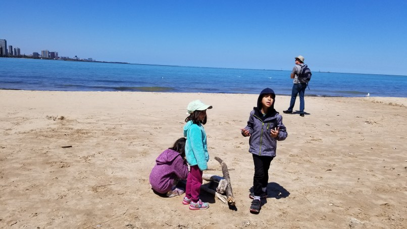 Three children playing in the sand while their father looks out onto Lake Michigan