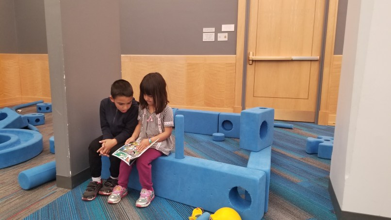 Boy and girl sitting on foam blocks and looking at a comic book together at the Harold Washington Public library, downtown Chicago.