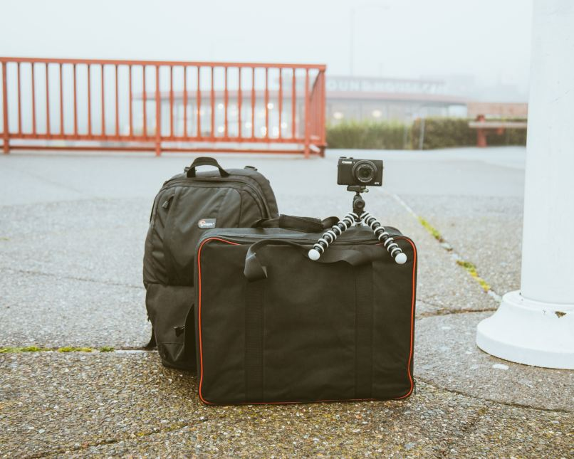 Backpack and luggage bag on the ground. A camera on a miniature tripod is sitting on top of the luggage bag. Photo by Dane Deaner on Unsplash