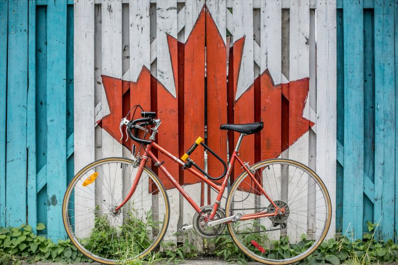 bicycle in front of a large red maple leaf painted on a wooden fence