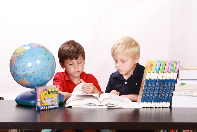 """Two boys sitting at a table looking at a book together. To their right is a globe, and teo their left are several """"Childcraft"""" books. Photo by White77 on Pixabay. This post is The Ultimate List of Free Homeschooling Resources on www.marianamcdougall.com"""