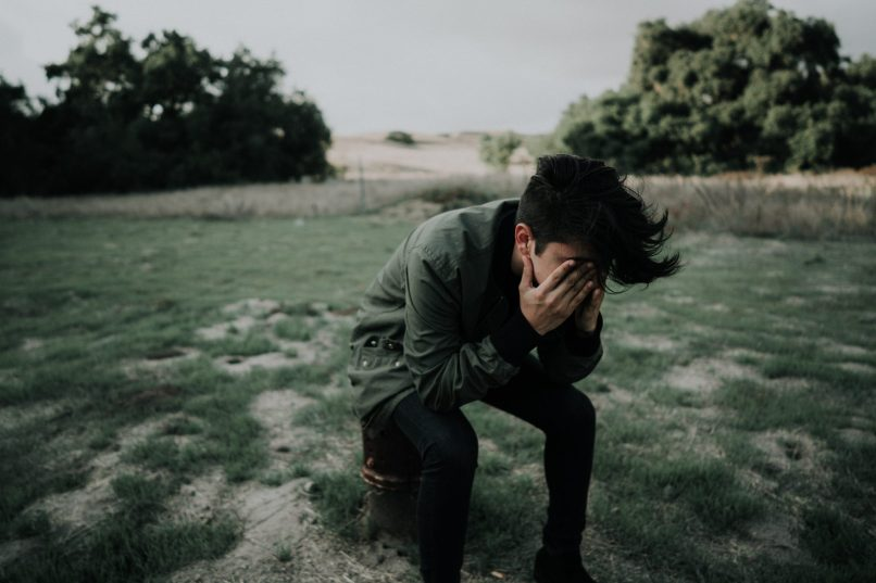 Man with head in his hands, sitting in a field. Photo by Francisco Gonzalez on Unsplash. Heavy Metal bands advocating for suicide prevention, www.marianamcdougall.com
