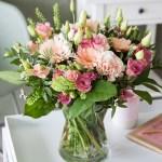 Blomsterbukett med vårlige nyanser av rosa og aprikos