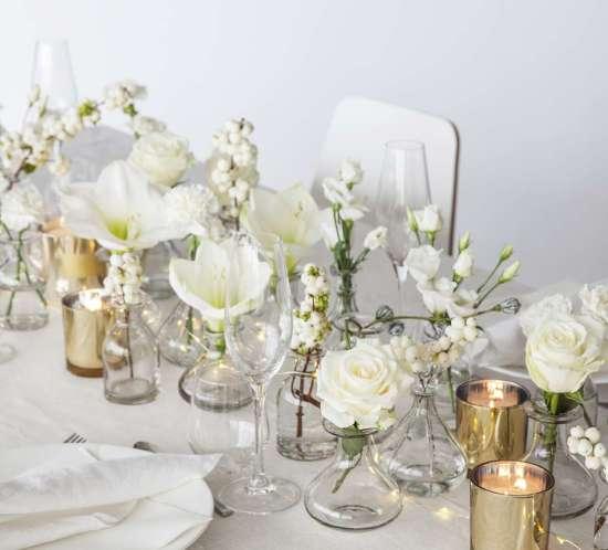 borddekking-med-hvite-blomster-langs-midten-av-bordet